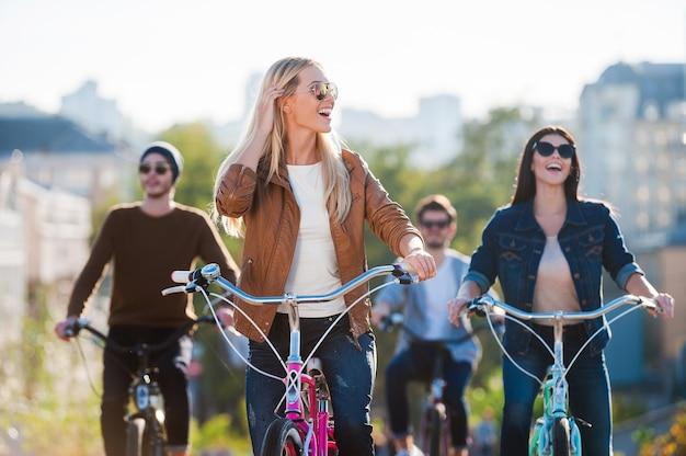 Zorgeloos genieten met vrienden. mooie jonge glimlachende vrouw die fietst en wegkijkt terwijl haar vrienden op de achtergrond rijden