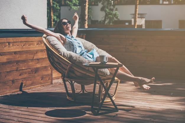 Zorgeloos genieten. mooie jonge vrouw ontspannen in een grote comfortabele stoel op haar buitenhuisterras