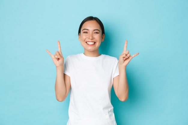Zorgeloos grappig en vrolijk mooi aziatisch meisje in wit t-shirt, tong en rock-n-roll gebaar tonen, genieten van geweldig festival, blij en verbaasd kijken, feesten over blauwe achtergrond.