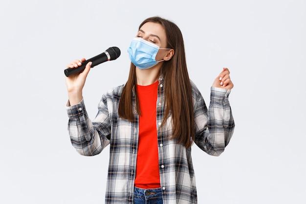 Zorgeloos jong meisje in medische masker, zingen met microfoon, ogen sluiten, genieten van karaoke