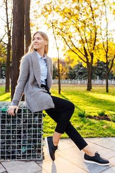 Zorgeloos jonge vrouw zittend op een bankje en lachen. mooi meisje in een goed humeur, op een herfstdag, genietend van het mooie weer.