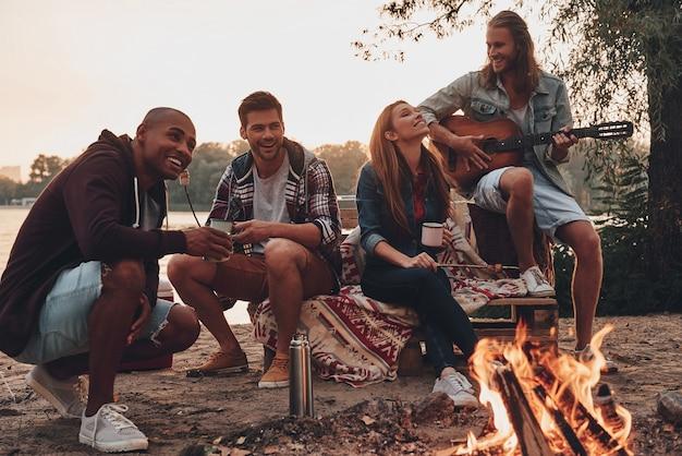 Zorgeloos kamperen. groep jongeren in vrijetijdskleding die lacht terwijl ze genieten van een strandfeest bij het kampvuur
