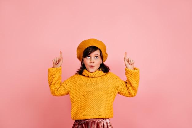 Zorgeloos kind dat in gele baret omhoog kijkt. kaukasisch kind dat grappige gezichten op roze muur maakt.
