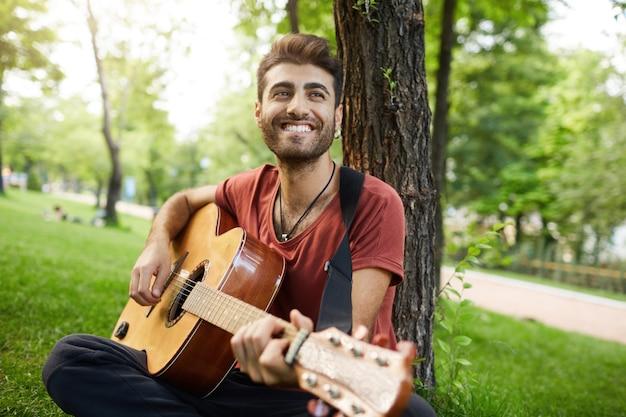 Zorgeloos knappe jongen gitaarspelen in park