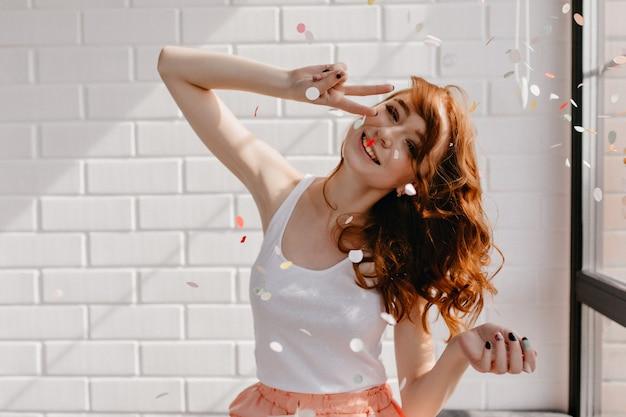 Zorgeloos krullend meisje poseren met vredesteken thuis. positieve roodharige dame die oprechte emoties uitdrukt.