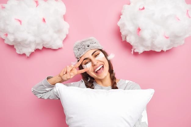 Zorgeloos lachend meisje wordt 's ochtends wakker, kantelt haar hoofd en maakt vredesgebaar