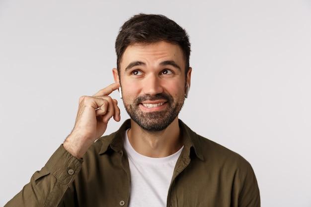 Zorgeloos lachende knappe bebaarde volwassen man in jas, dromerig en vreugdevol opzoeken, draadloze oortelefoon aanraken om af te stemmen, het volume te veranderen of gelukkig te eindigen
