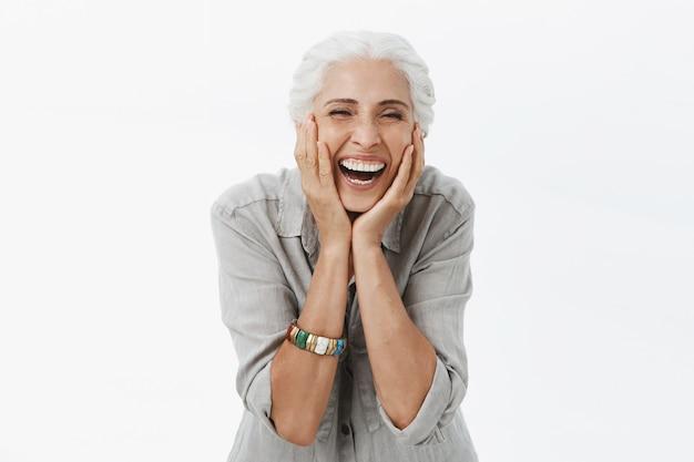 Zorgeloos lachende senior vrouw op zoek blij, gezicht aanraken
