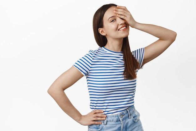 Zorgeloos lachende vrouw bedekt één oog met de hand, kijkt gelukkig naar de voorkant, houdt de hand op de taille, draagt een gestreept zomert-shirt, staat over een witte muur