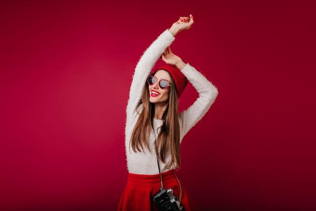 Zorgeloos langharig meisje in een rode hoed poseren met handen omhoog op bordeauxrode ruimte