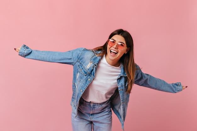 Zorgeloos meisje dat in zonnebril op roze achtergrond lacht. studio shot van opgewonden jonge vrouw in jeans met plezier.
