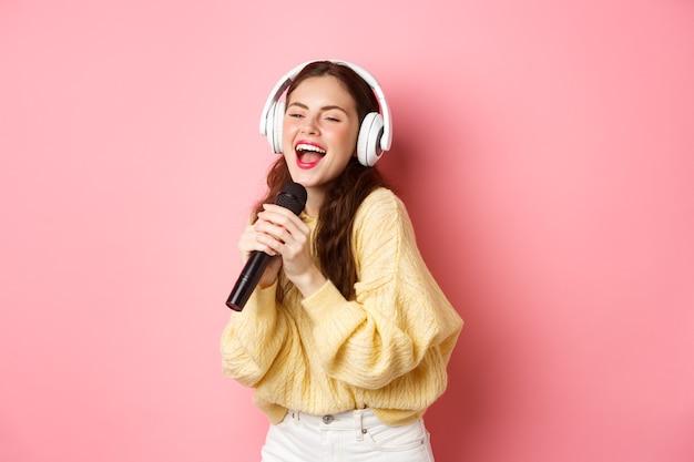 Zorgeloos meisje dat van karaokeavond geniet, lied in microfoon zingt, draadloze hoofdtelefoons draagt, die zich tegen roze muur bevindt.