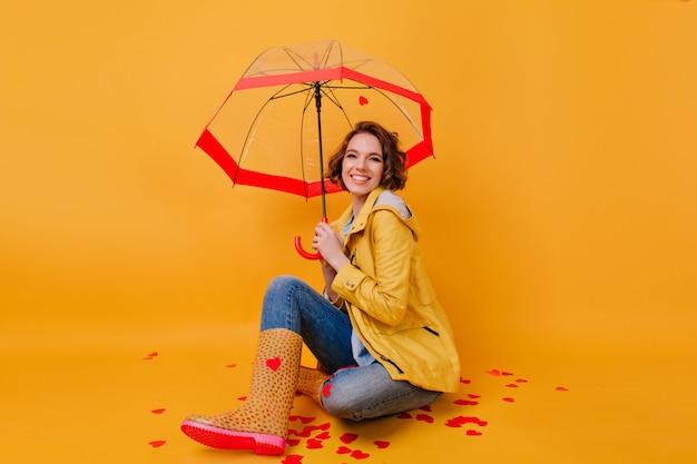 Zorgeloos meisje in stijlvolle herfst outfit poseren met benen gekruist onder parasol. binnenportret van innemende dame die met paraplu op gele muur lacht.