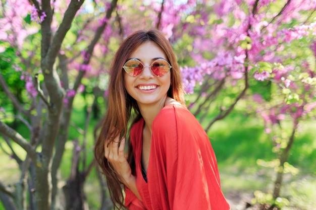 Zorgeloos meisje in stijlvolle strooien hoed en koraal jurk genieten van de lentedag in zonnige tuin op bloeiende boom