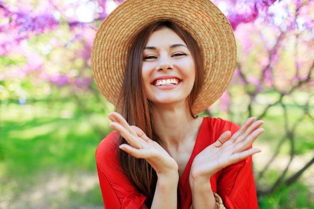 Zorgeloos meisje in stijlvolle strooien hoed en koraal jurk genieten van wale lentedag in zonnige tuin op bloeiende boom