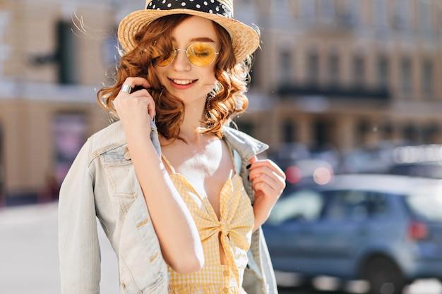 Zorgeloos meisje in zonnebril en spijkerjasje genieten van warme lentedag. buiten schot van prachtige gember jonge vrouw die zachtjes glimlacht tijdens wandeling.