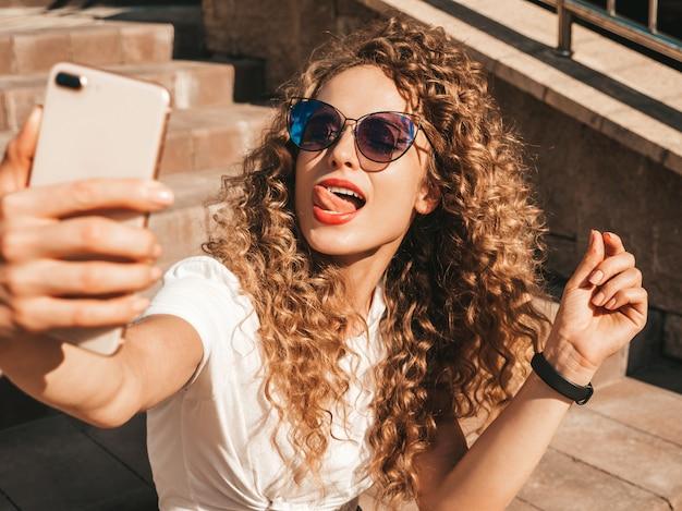 Zorgeloos meisje zittend op de trap in de straat een selfie te nemen