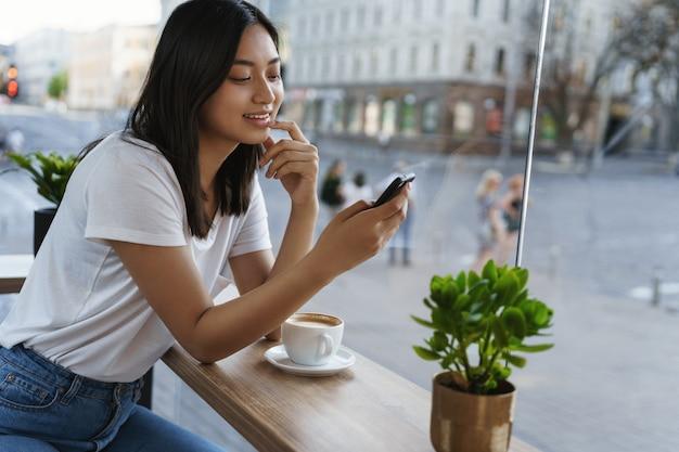 Zorgeloos modern meisje met behulp van smartphone, alleen café zitten. Premium Foto