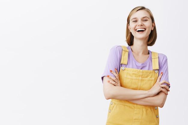 Zorgeloos mooi lachend meisje dat pret heeft, gelukkig kijkt over witte muur