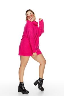 Zorgeloos. mooie jonge vrouwen helderroze comfortabele sweater, geïsoleerde lange koker