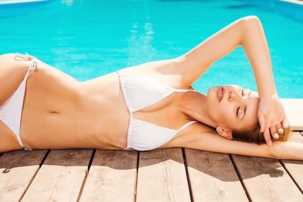 Zorgeloos ontspannen bij het zwembad. mooie jonge vrouw in witte bikini die bij het zwembad ligt en de ogen gesloten houdt