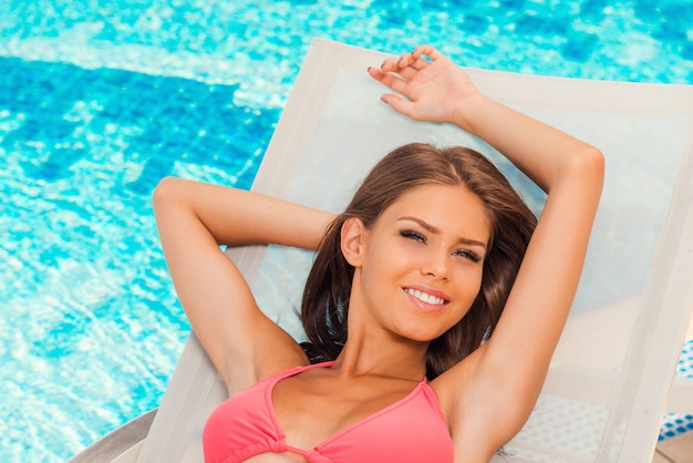 Zorgeloos ontspannen. bovenaanzicht van mooie jonge vrouw in bikini ontspannen op de ligstoel bij het zwembad