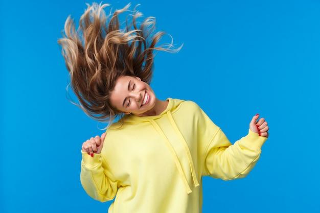 Zorgeloos ontspannen en vrolijk mooi blond meisje hoofd schudden, dansen en springen van geluk, plezier hebben op een geweldig feest of muziekconcert, staand