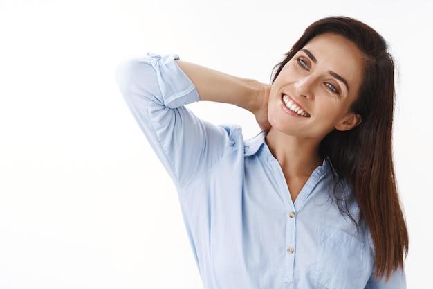 Zorgeloos ontspannen tedere ambitieuze brunette vrouw van middelbare leeftijd, vreugdevol uitrekken, werk afmaken blij thuiskomen, hoofd kantelen, nek masseren, glimlachen, overweeg linker copyspace, witte muur