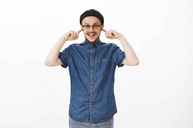 Zorgeloos onverschillig knappe stijlvolle man met snor in zwarte muts en bril die oren bedekt met wijsvinger niet luisteren