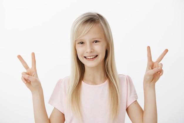 Zorgeloos positief vrouwelijk kind met blond haar in vrijetijdskleding, overwinning of vredesgebaren met beide handen tonend en vrolijk glimlachend, blij staande tegen grijze muur