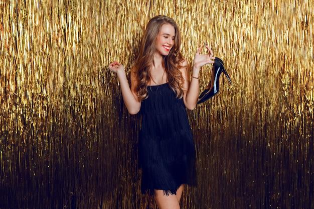 Zorgeloos prachtige blonde vrouw met glas cocktail en schoenen in de hand.