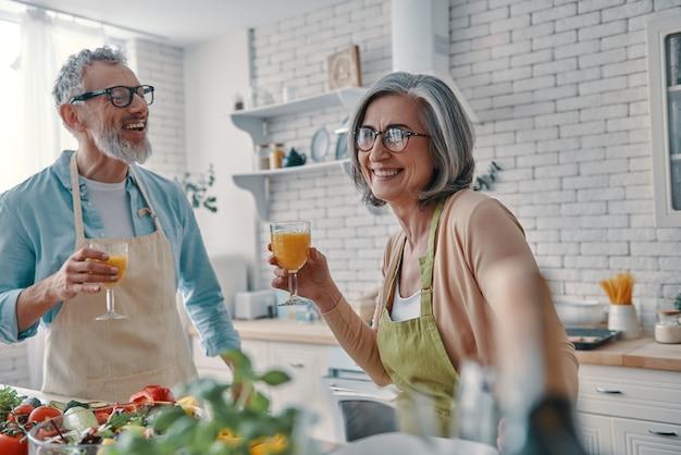 Zorgeloos senior koppel in schorten die elkaar roosteren met sinaasappelsap en een gezond diner bereiden terwijl ze thuis tijd doorbrengen