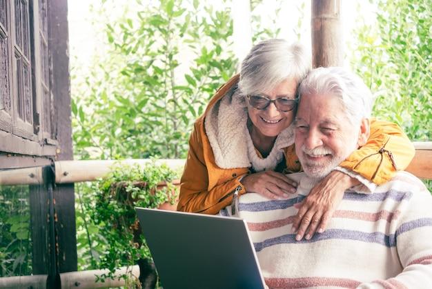 Zorgeloos senior paar knuffelen in houten balkon van bergchalet terwijl man met laptopcomputer. kaukasische ouderen ontspannen buiten in de bergen