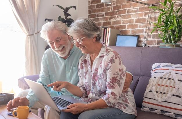 Zorgeloos senior paar met behulp van laptopcomputer thuis, zittend op de bank. bakstenen muur op achtergrond