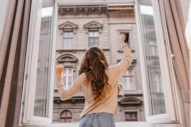 Zorgeloos slank meisje in spijkerbroek dansen naast raam met kopje koffie