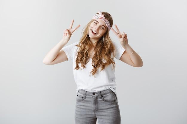 Zorgeloos stijlvol blond meisje dat van de zomer geniet, gelukkig vredesgebaar toont