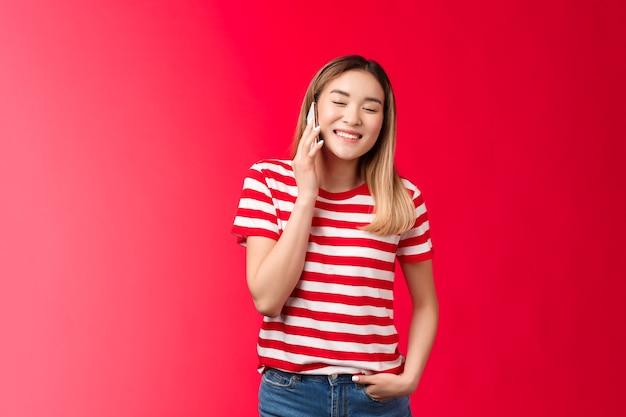 Zorgeloos vriendelijk knap blond aziatisch meisje met grappig gesprek pratende telefoon ogen dicht jo...