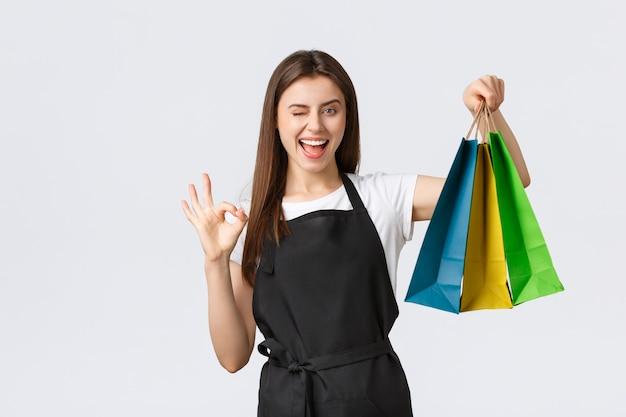 Zorgeloos, vriendelijk ogende vrouwelijke kassier in zwart schort garandeert kwaliteit of gekochte artikelen, knipoog en toont goed teken terwijl ze papieren zakken overhandigt met bestelling van de klant, witte achtergrond
