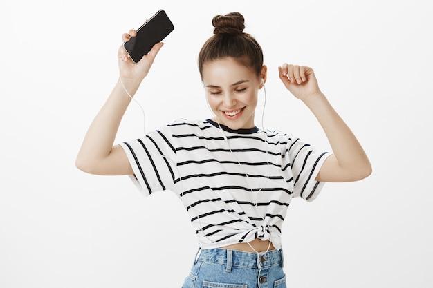 Zorgeloos vrij kaukasisch meisje dansen in hoofdtelefoons met smartphone