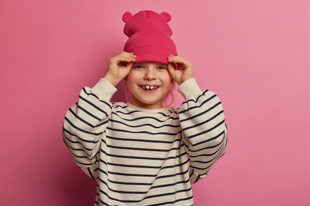 Zorgeloos vrolijk meisje zet roze hoed met oren op, lacht vriendelijk, tevreden met nieuwe outfit, praat met beste vriend, draagt oversized gestreepte trui, drukt goede emoties uit, poseert alleen binnen