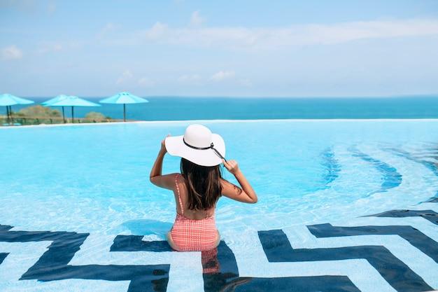 Zorgeloos vrouw in bikini en een strooien hoed ontspannen in het oneindige zwembad kijken naar zeezicht. luxe resort.