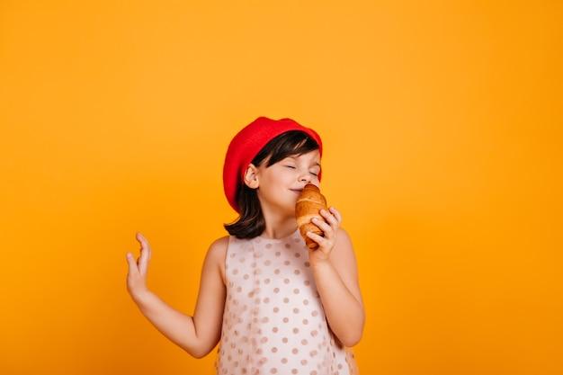 Zorgeloos vrouwelijk kind dat croissant eet. schattig jong geitje dat zich op gele muur bevindt.