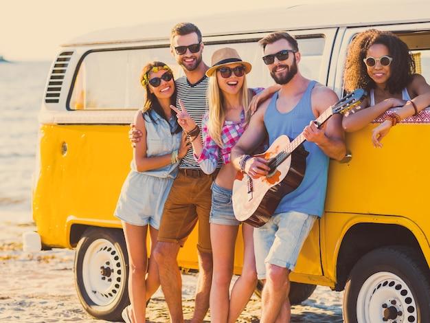 Zorgeloos weekend met vrienden. groep vrolijke jonge mensen die zich aan elkaar hechten en glimlachen terwijl ze leunen op hun retro-stijl minibusje met de zee op de achtergrond