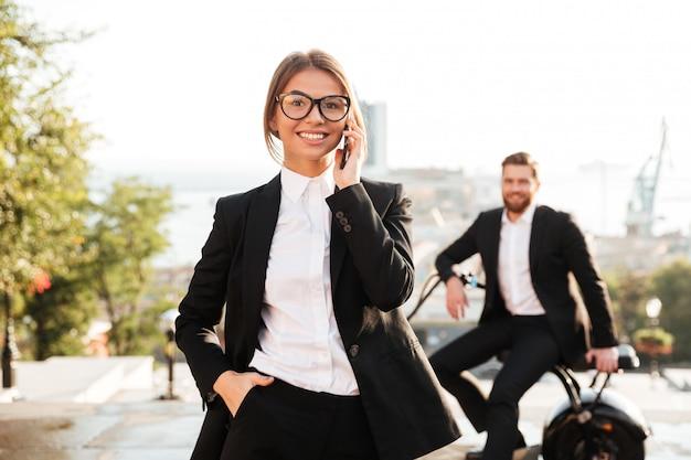 Zorgeloos zakenvrouw poseren buitenshuis en praten via de telefoon