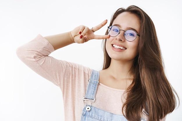 Zorgeloze aantrekkelijke jonge charismatische 20s-vrouw in een bril met bruin haar die overwinning of vredesgebaar toont in de buurt van gezicht dat het hoofd vreugdevol kantelt en tevreden glimlacht aan de voorkant die over grijze muur poseert.