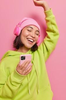 Zorgeloze aziatische vrouw heeft vrolijke stemmingsdansen met ritme van muziek maakt gebruik van moderne mobiele telefoons en koptelefoon draagt hoed en sweatshirt geïsoleerd over roze muur brengt vrije tijd door met favoriete afspeellijst