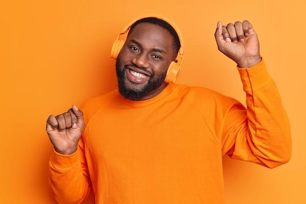 Zorgeloze bebaarde man dikke baard en brede glimlach steekt armen op danst zorgeloos beweegt met het ritme van de muziek luistert naar muziek uit de afspeellijst via een hoofdtelefoon gekleed in een oranje trui