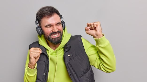 Zorgeloze bebaarde man heeft plezier geniet van favoriete muziek maakt ja gebaar houdt armen omhoog dansen