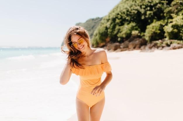 Zorgeloze blanke dame poseren met plezier op het strand. vrij vrouwelijk model met gebruinde huid die rond aan zandstrand loopt.