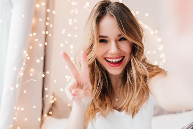 Zorgeloze blanke vrouw met lichte make-up poseren met vredesteken. binnen schot van prachtig krullend meisje selfie maken in haar kamer. Gratis Foto